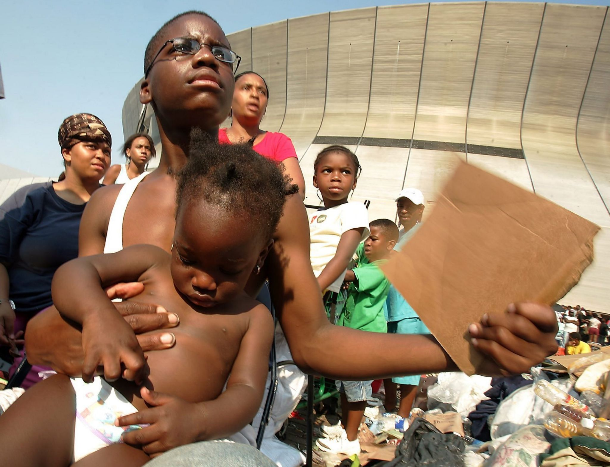 A young boy holds a smaller child outside the New Orleans Superdome