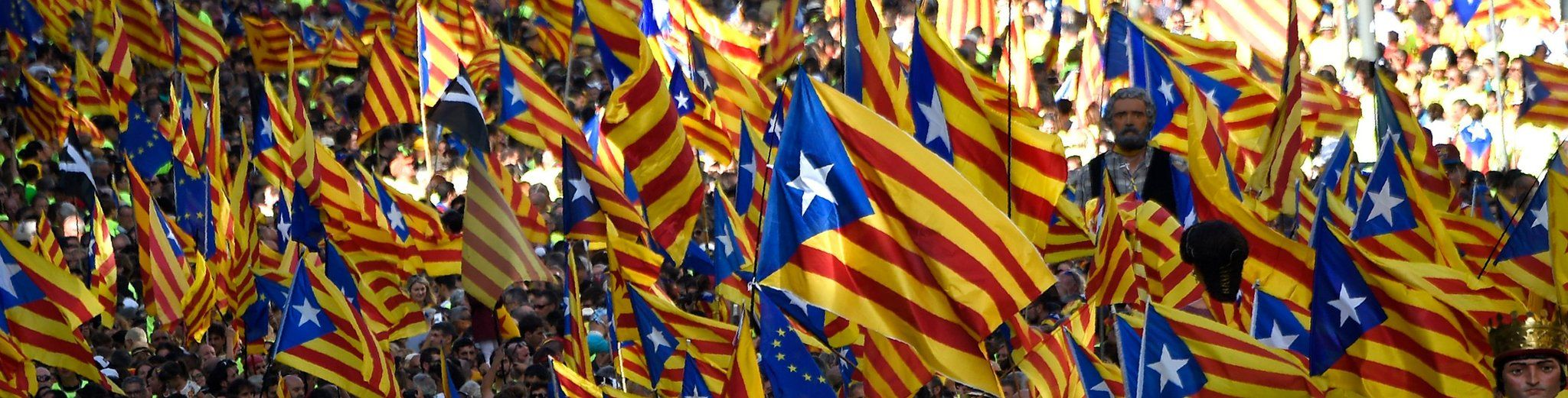 """People wave """"Esteladas"""" (pro-independence Catalan flags) as they gather during a pro-independence demonstration, on September 11, 2017 in Barcelona"""