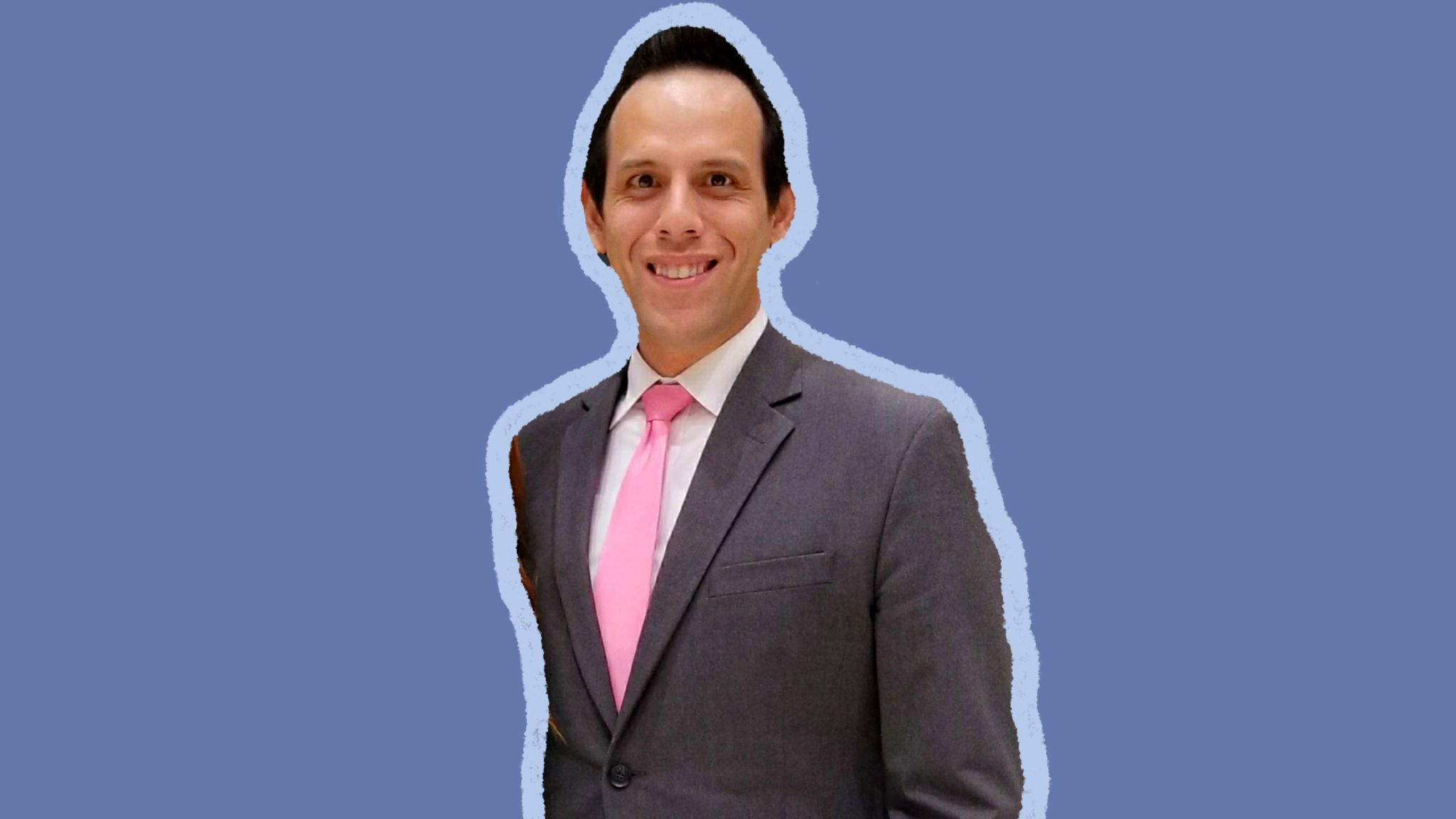 Brett Chapman standing with a suit and tie, and plain blue background
