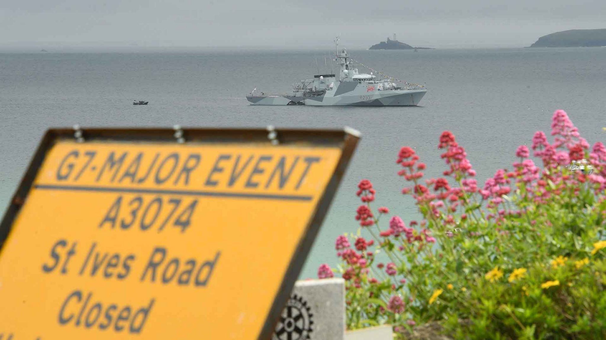 """Road sign says """"G7 major event"""" - behind it, a Navy cruiser in the sea off Carbis Bay"""