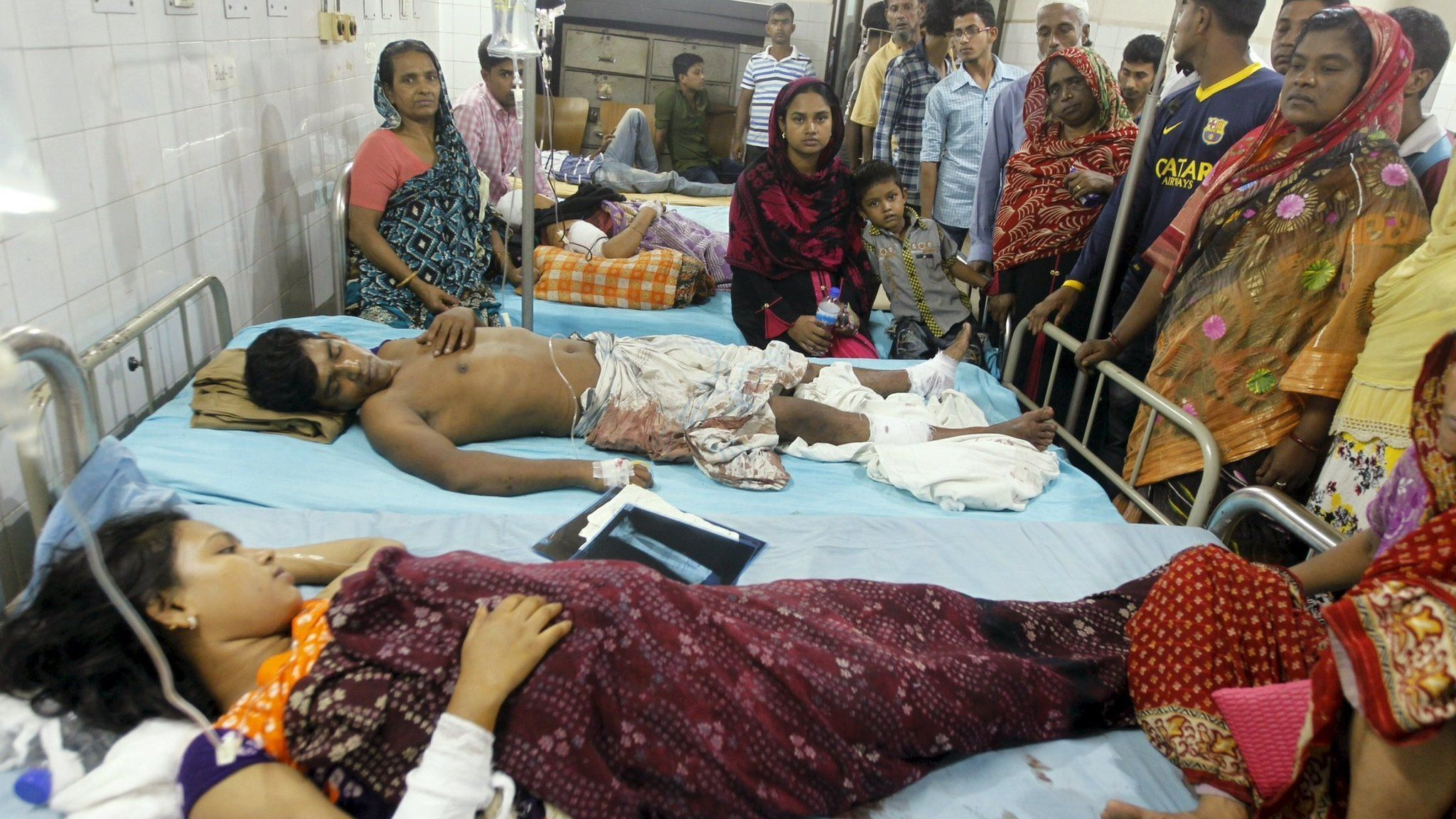 People who sustained injuries in a series of blasts are surrounded by their relatives at a hospital in Dhaka on 24 October 2015