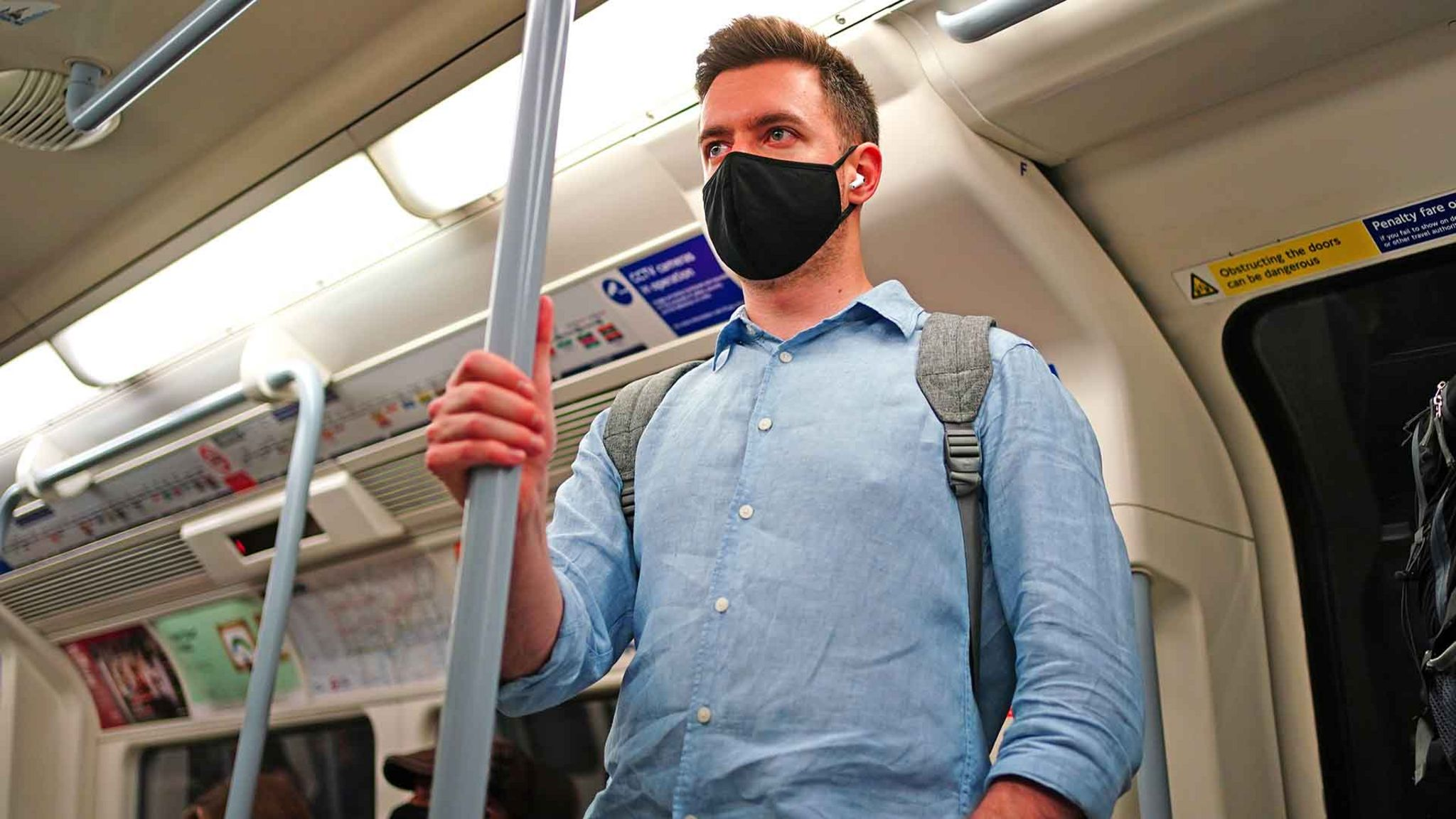 Man wearing a face mask on a London Underground train, 4 July 2021