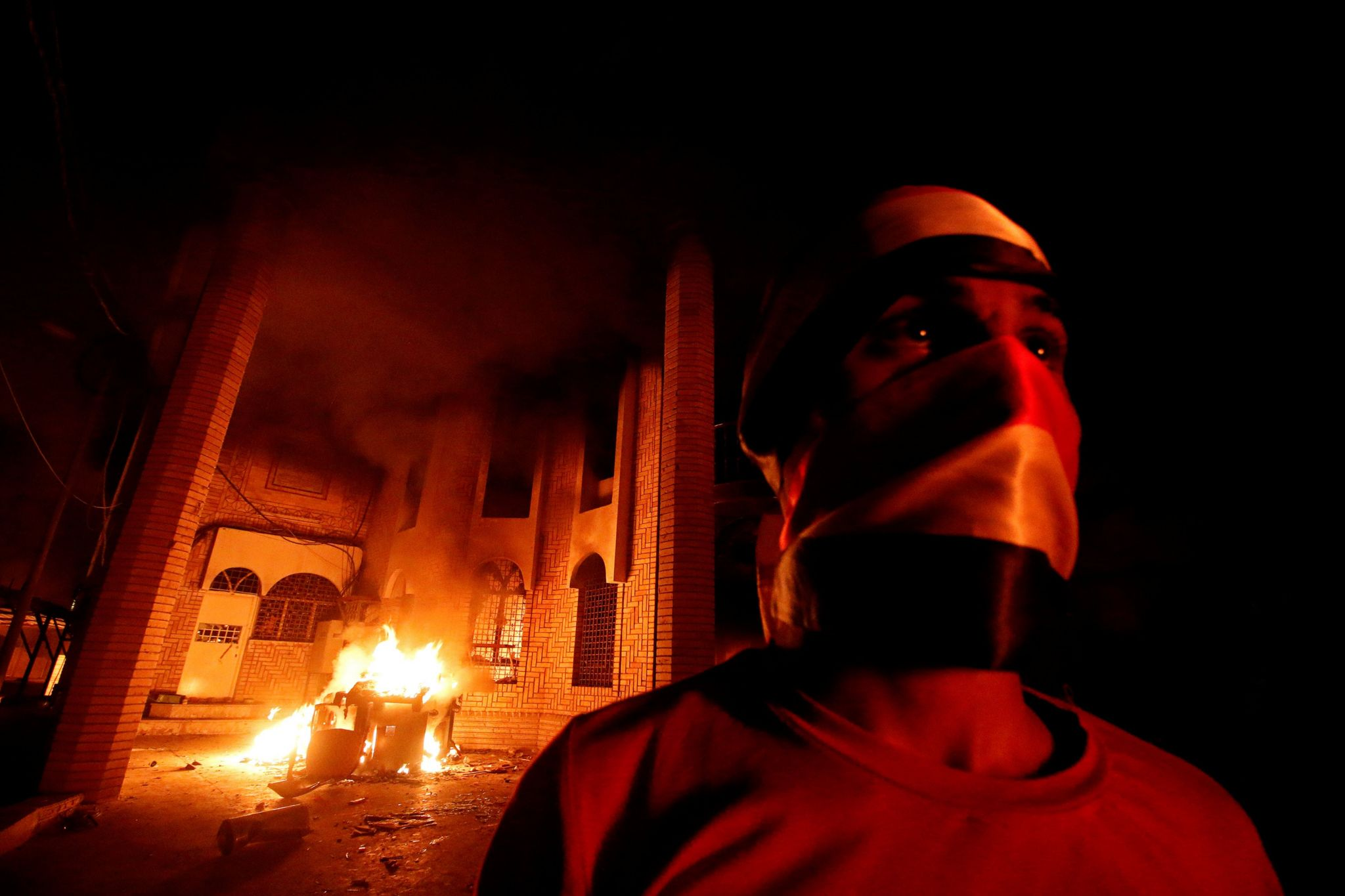 Iraqi protesters are seen near the burnt Iranian Consulate in Basra, 7 September 2018