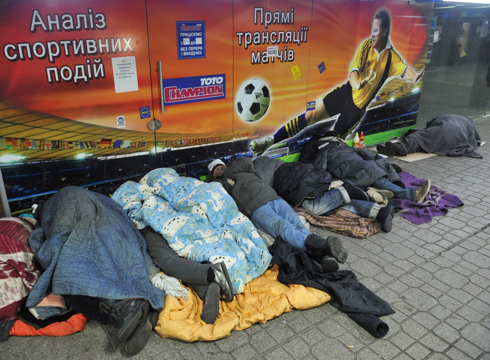 Homeless people sleeping in front of a building in Ukraine's capital Kiev on December 18, 2013.