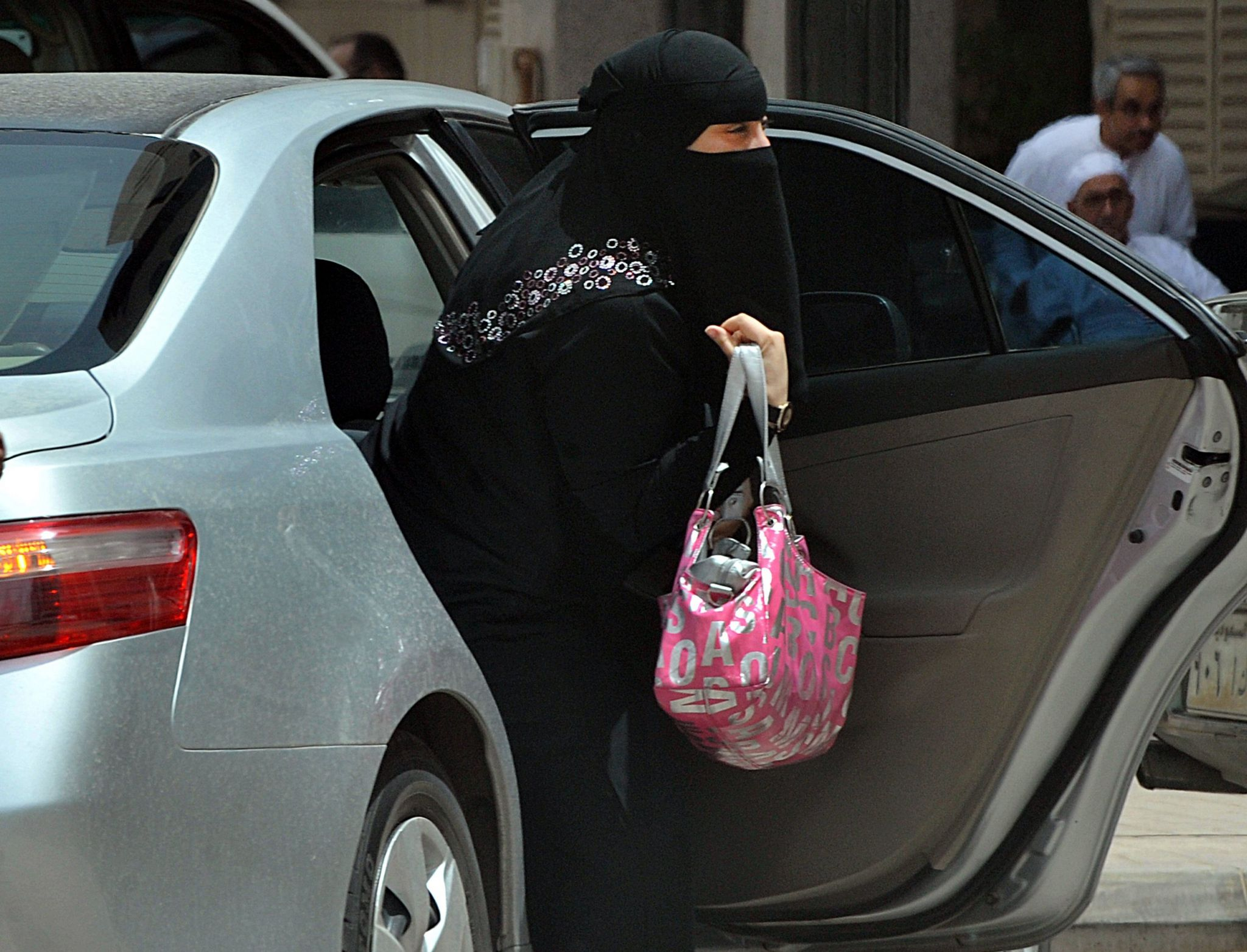 A Saudi woman gets out of a car after being given a ride by her driver in Riyadh on 26 May, 2011