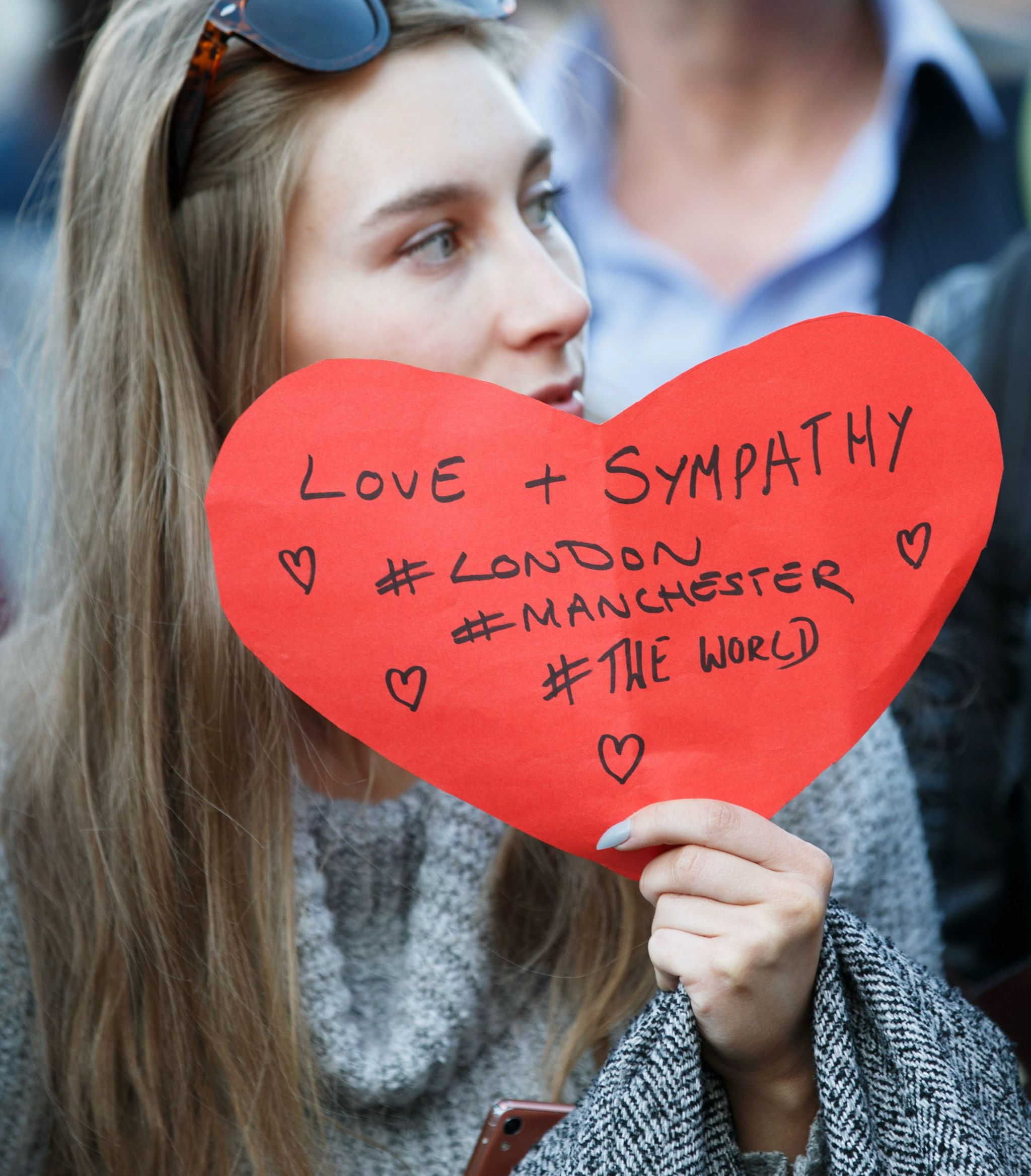 A woman holds a sign saying love and sympathy - London, Manchester and the world