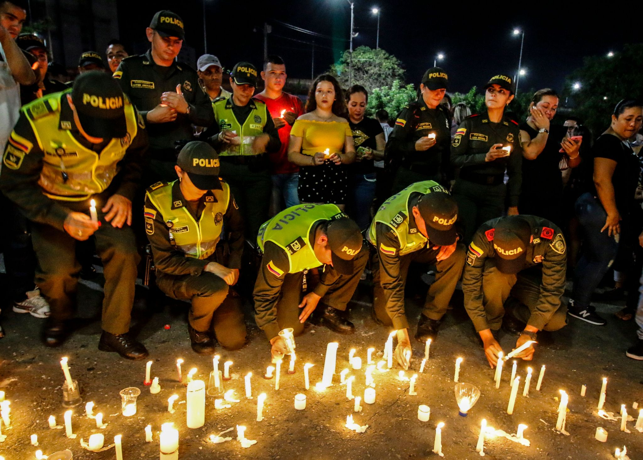 Police officers light candles in memory of their colleagues killed in an attack on the police academy