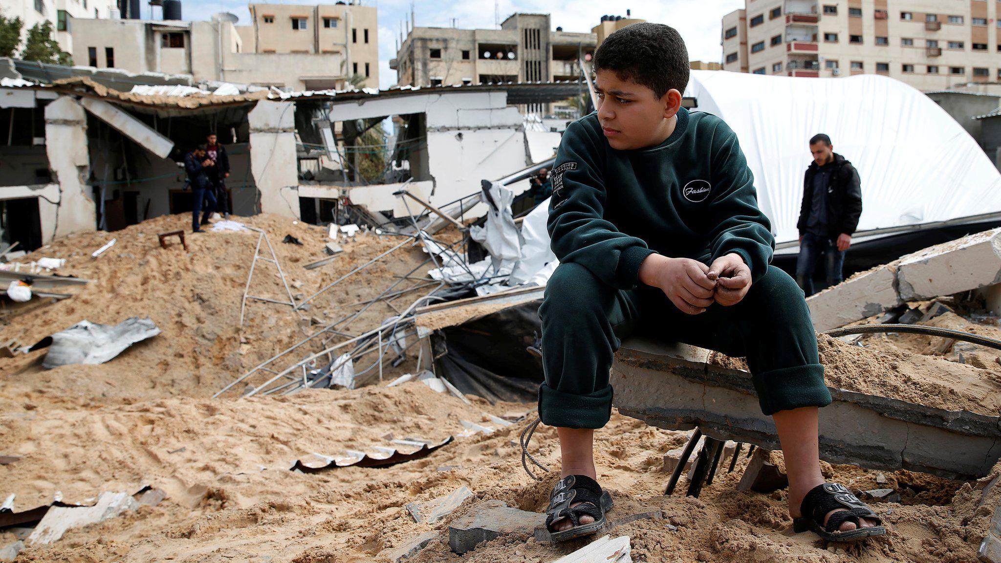 A Palestinian boy sits near a Hamas site in Gaza City destroyed in an Israeli air strike (15 March 2019)