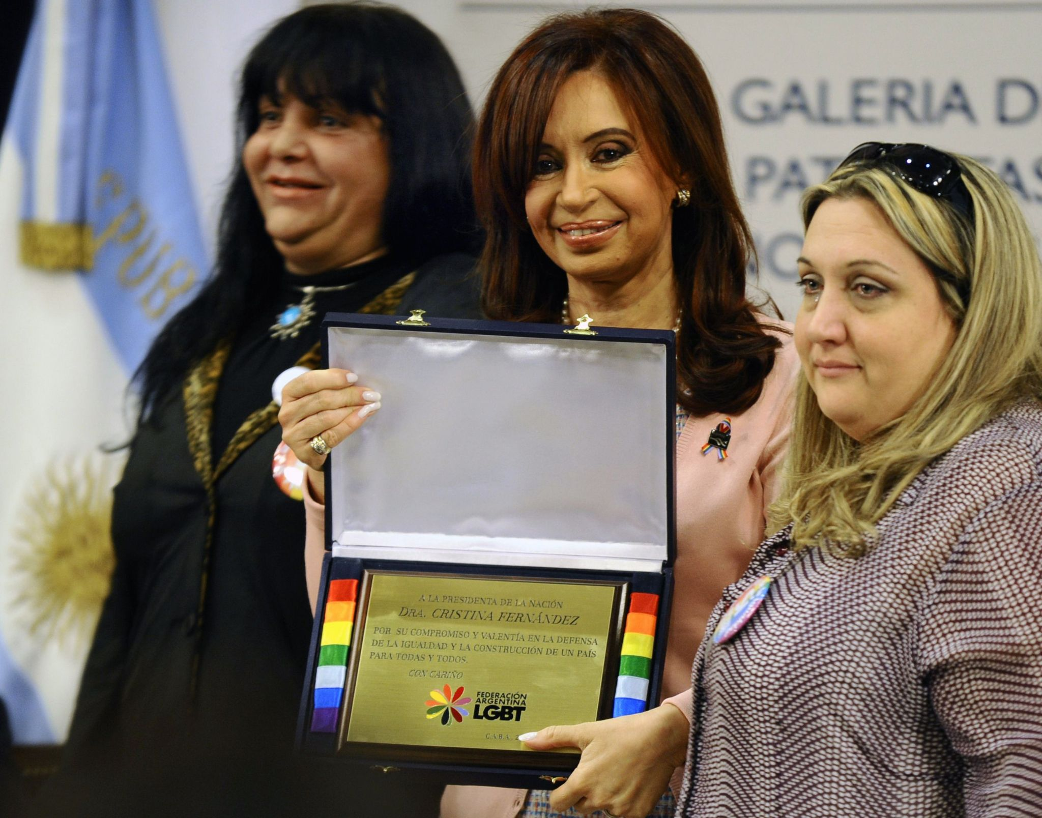 Cristina Fernandez de Kirchner holds a plaque given by members of the Argentine Federation of Lesbians, Gays, Bisexuals and Transvestites