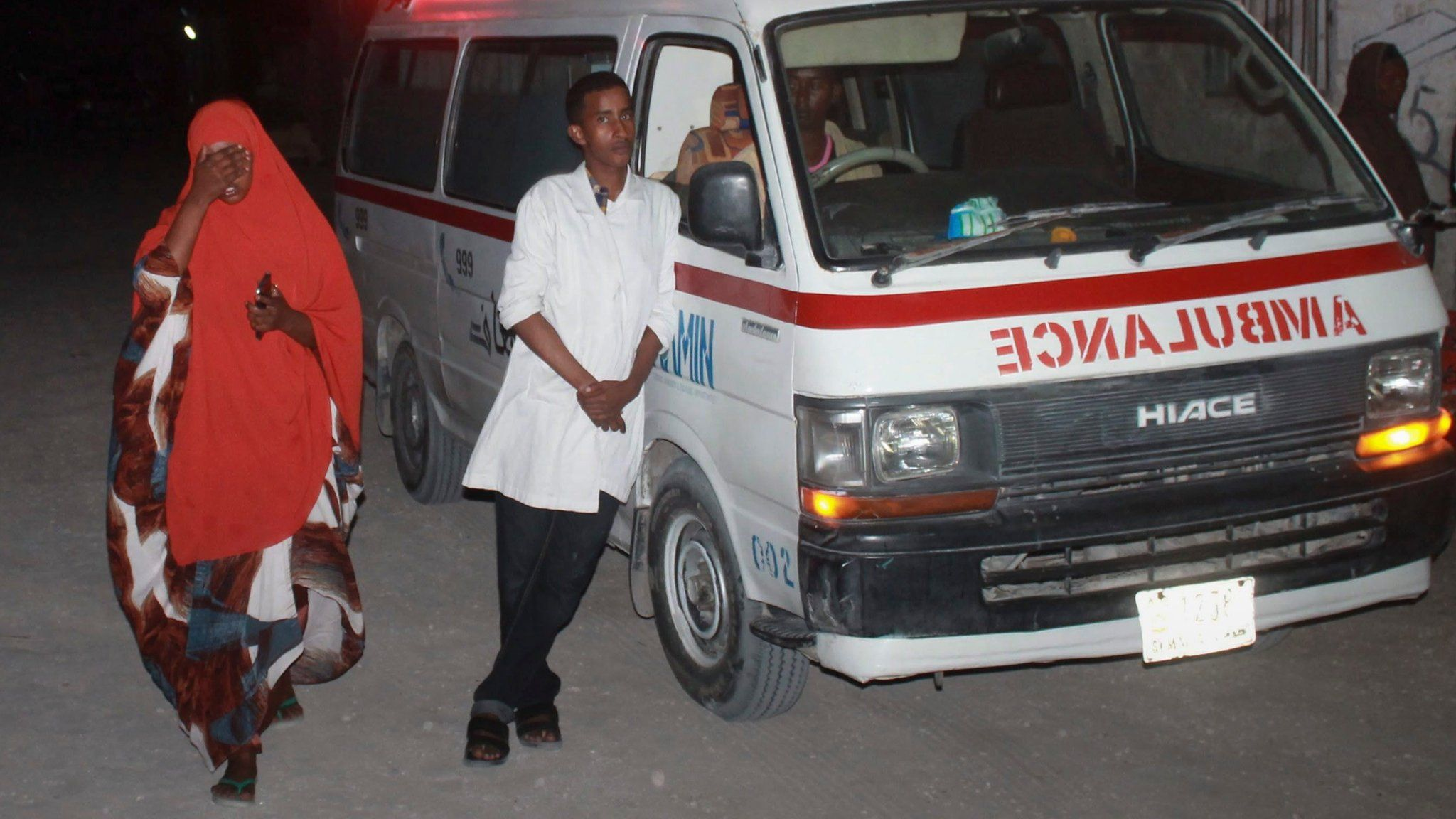 Ambulance workers stand by near the Lido beach where gunmen exploded a car bomb and opened fire at a restaurant in Mogadishu, Somalia, 21 January 2016.