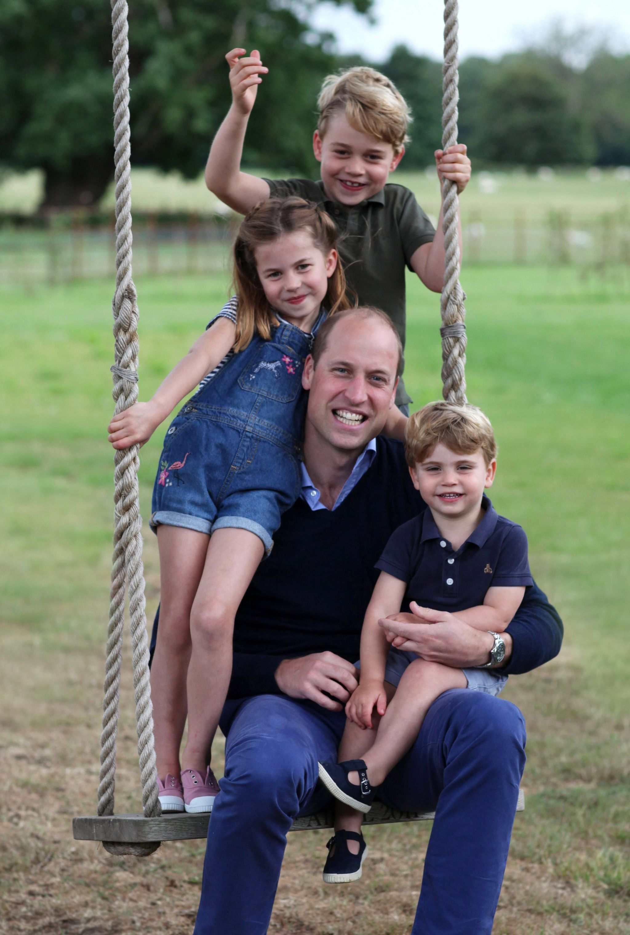 The Duke of Cambridge poses on a swing with Prince George, Princess Charlotte and Prince Louis