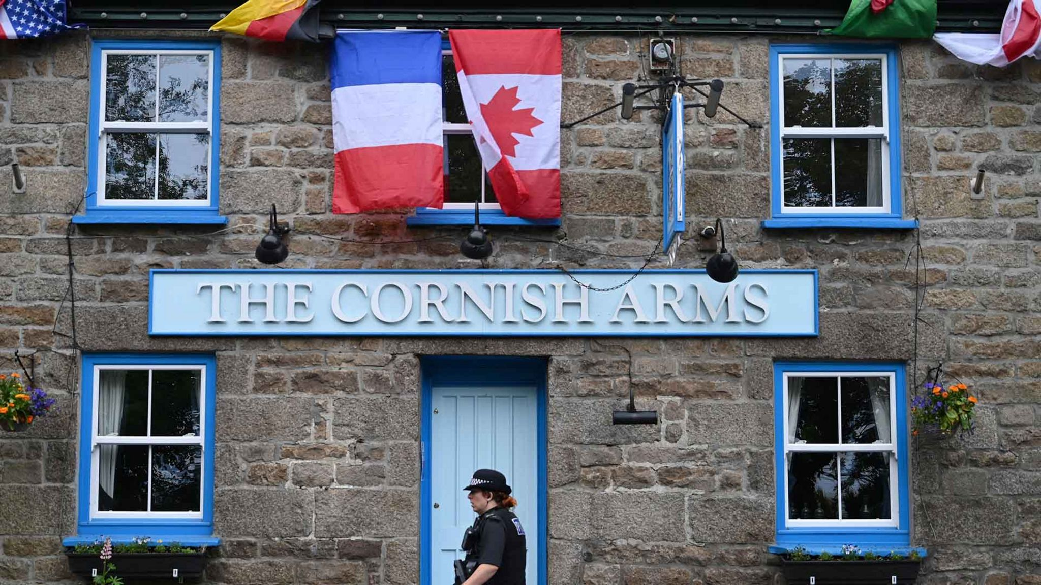 A British police officer walks past The Cornish Arms gastropub in St Ives, Cornwall on June 10, 2021,