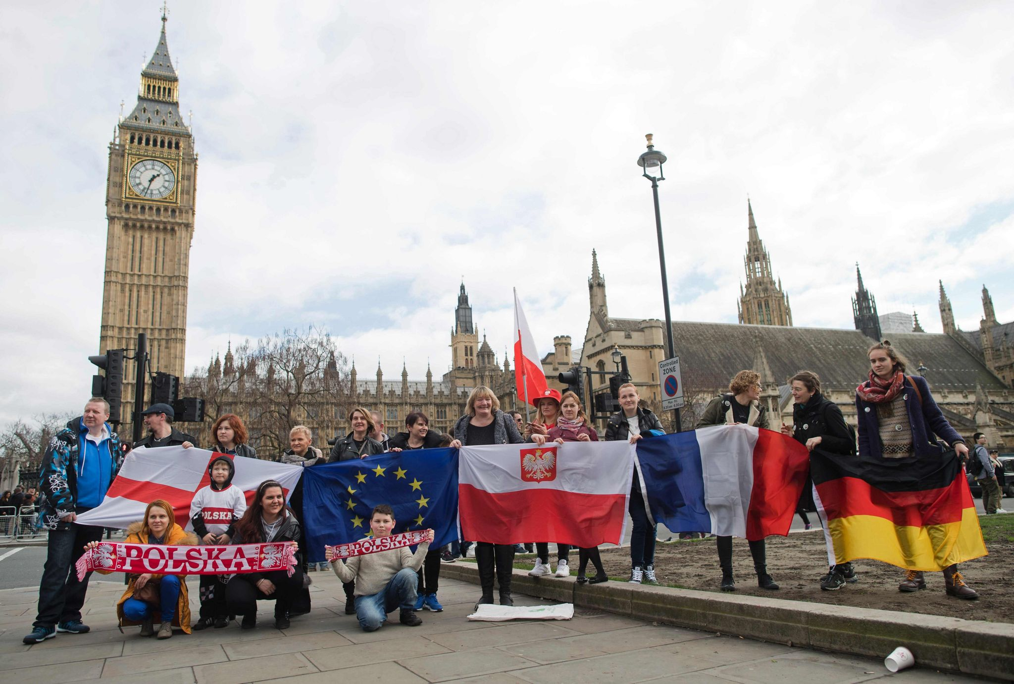 """Protestors pose for a photograph with flags from England, European Union, Poland, France and Germany in front of the Elizabeth Tower, better known as """"Big Ben"""", near the Houses of Parliament during a """"Flag Mob"""" demonstration in Parliament Square in central London on 20 February 2017"""