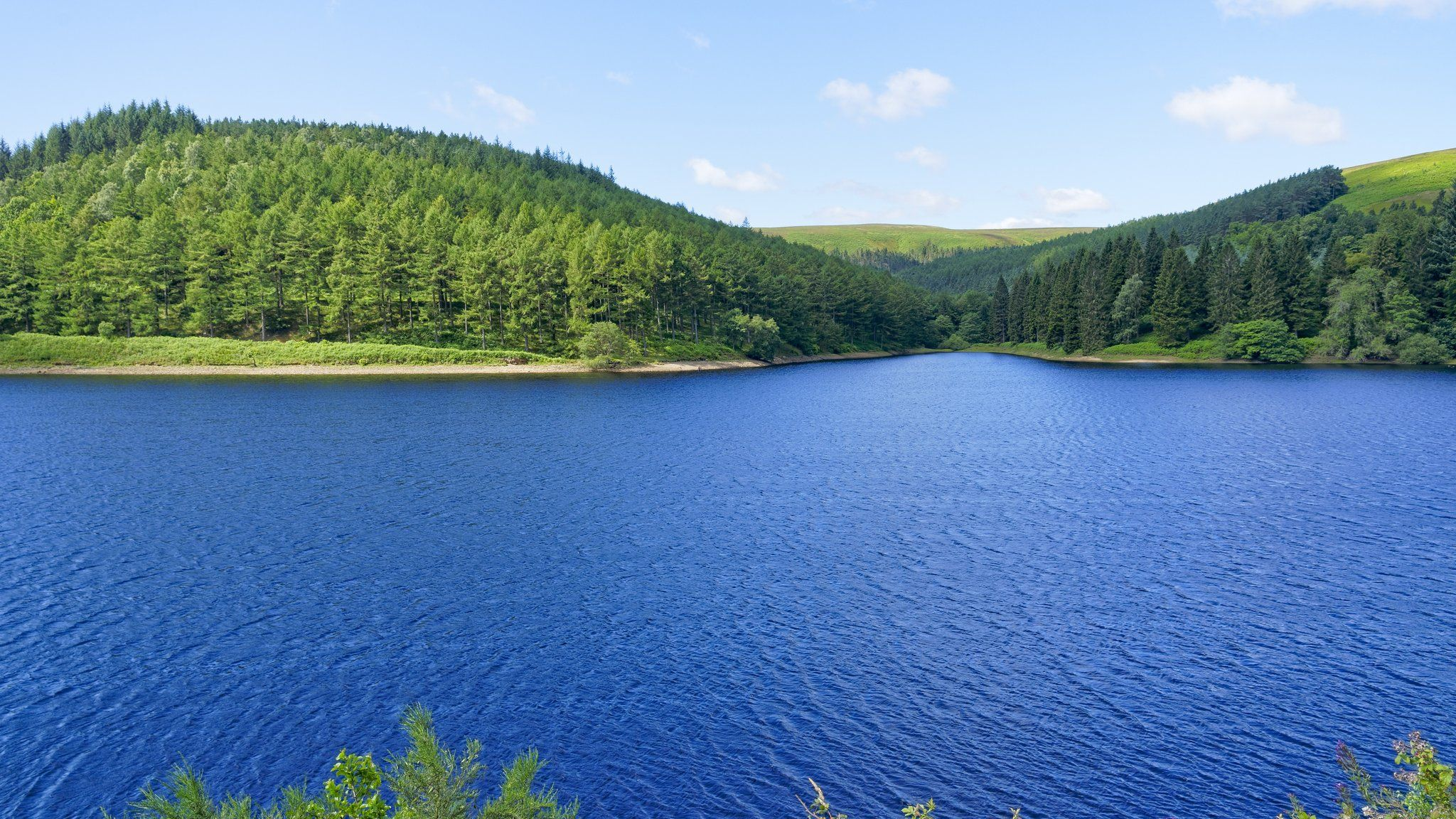 Over the breadth of Derwent Upper Reservoir to the wooded hills of Derbyshire