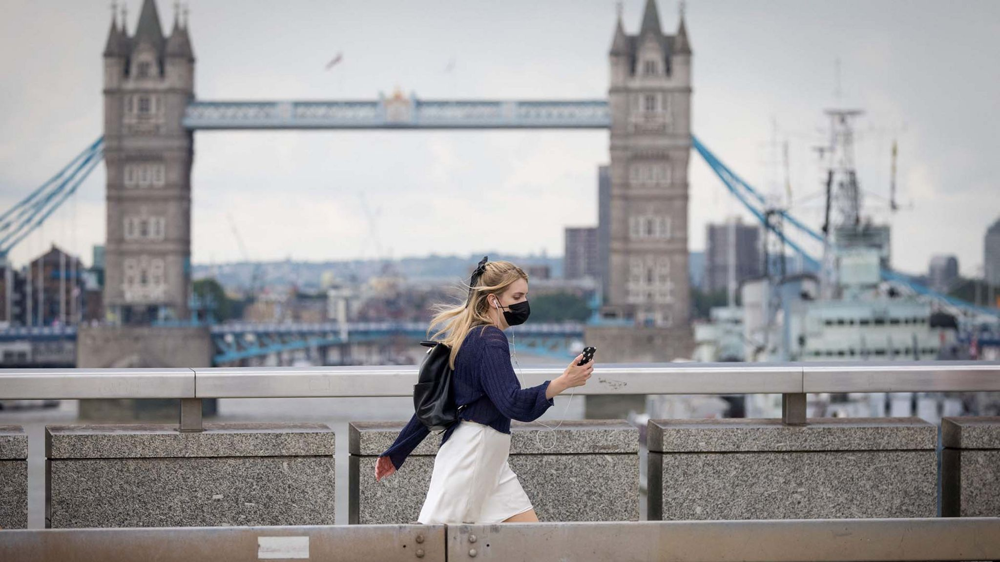 Woman in mask walks across London Bridge, with Tower Bridge and HMS Belfast in the background