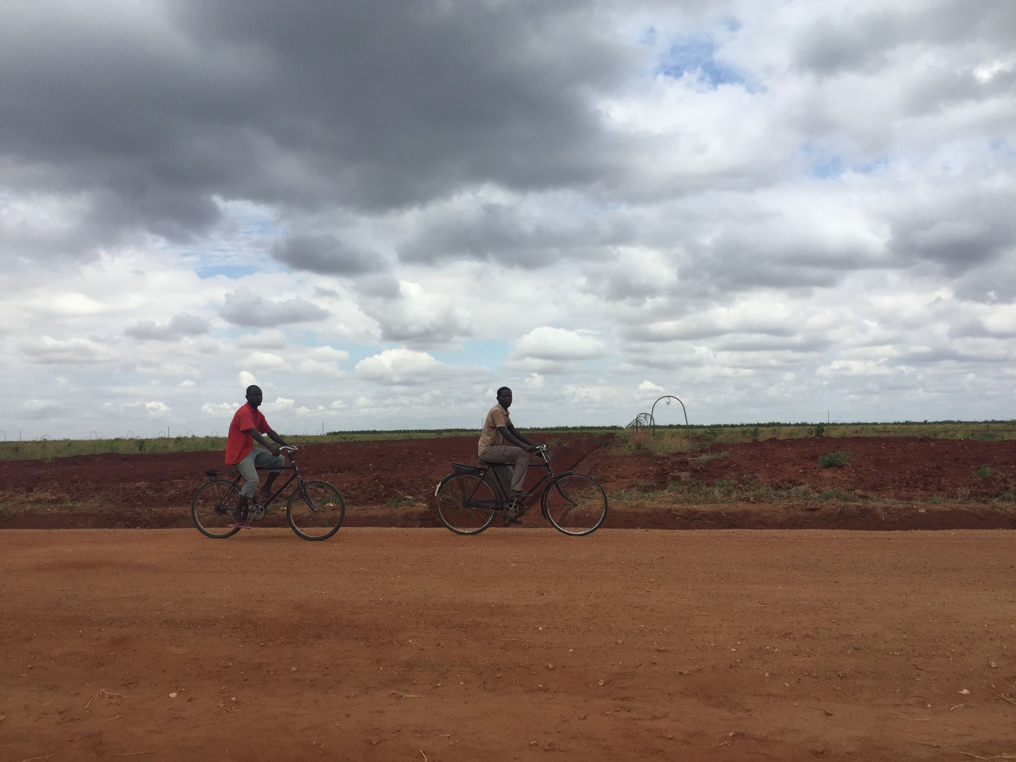 Boys riding bike in front of empty fields