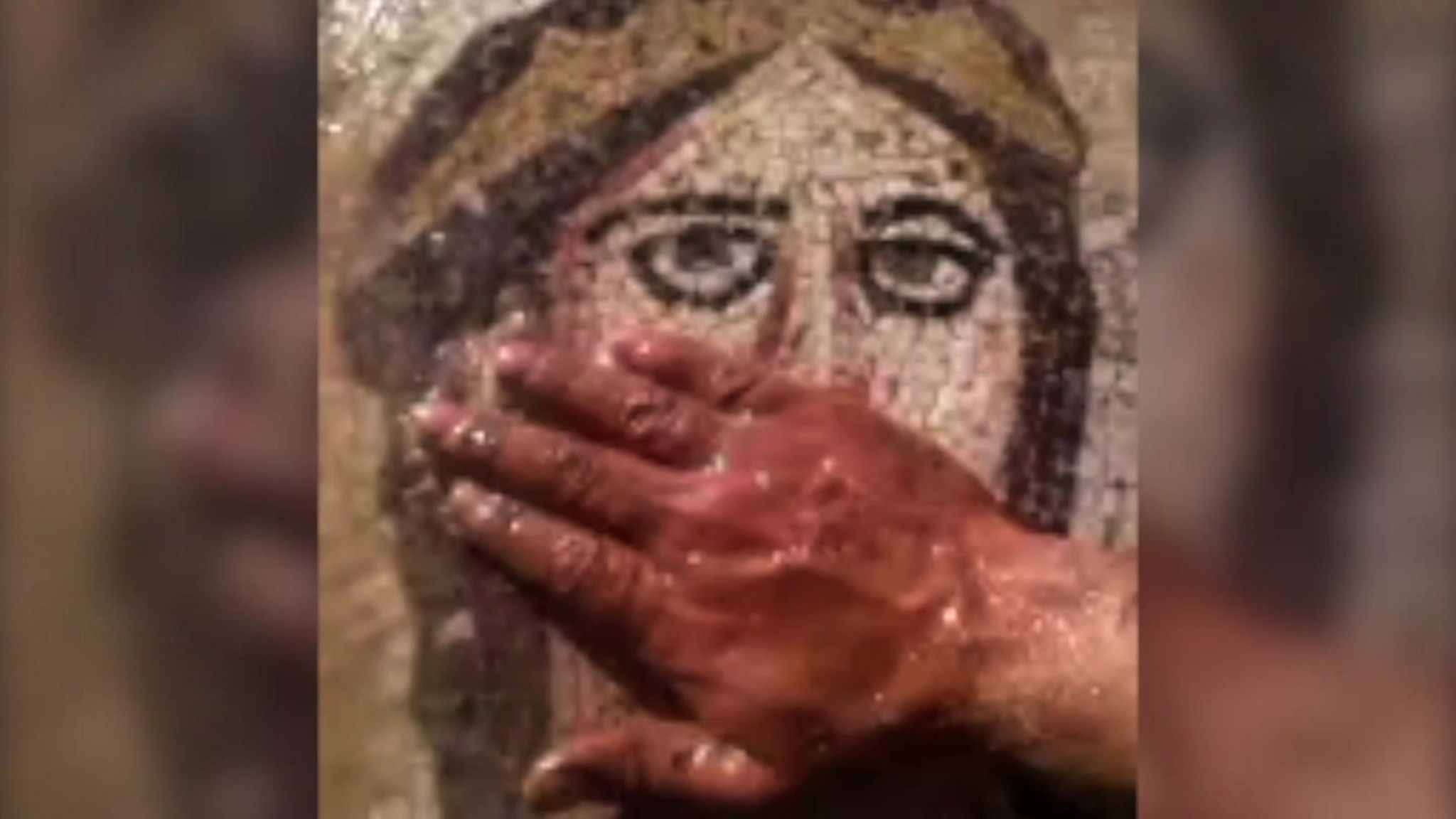Man's hand covers mouth of mosaic image of female face