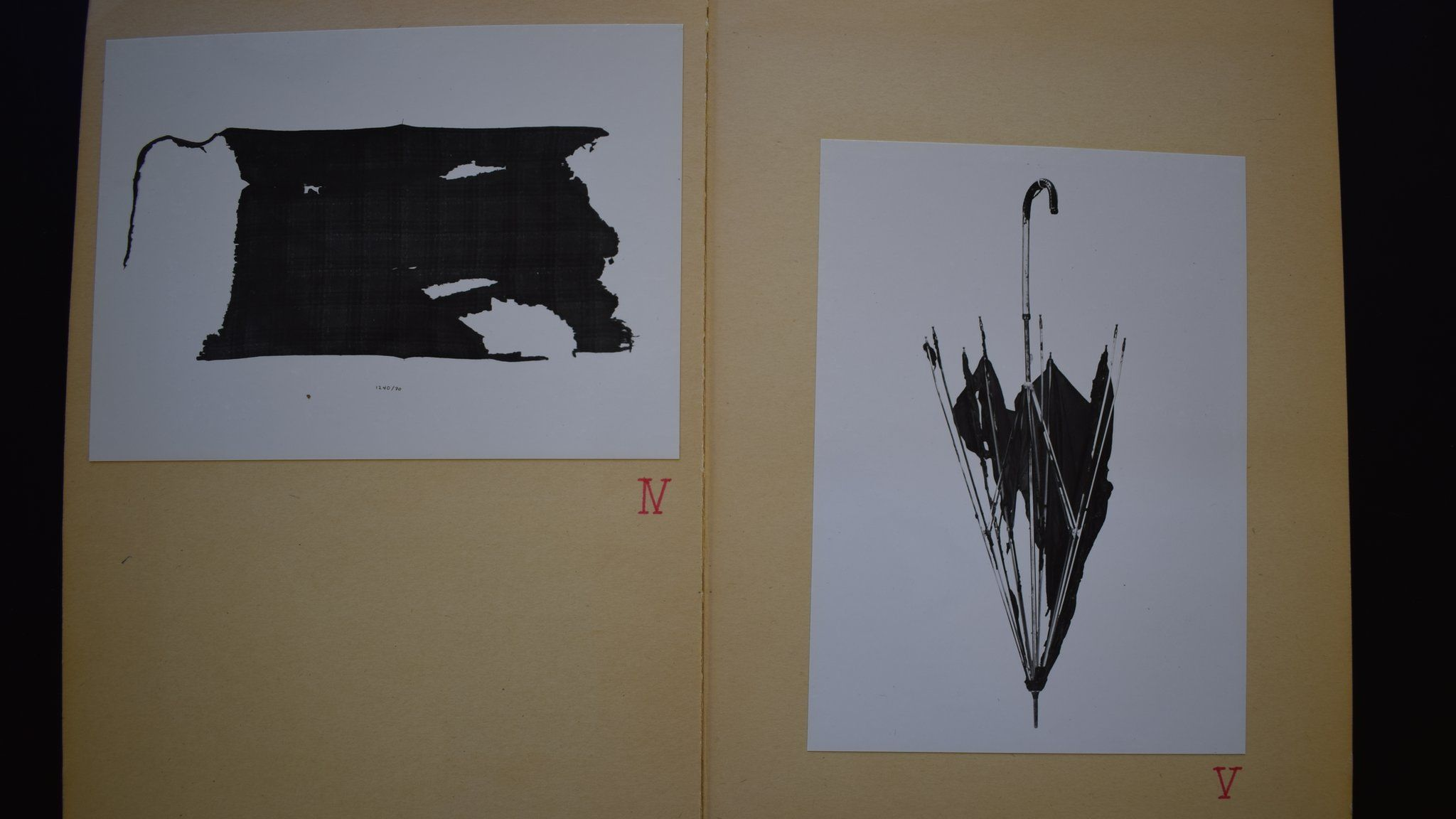 A photo of files at the Bergen State Archives shows police photos of burnt clothing and a damaged umbrella found at the scene