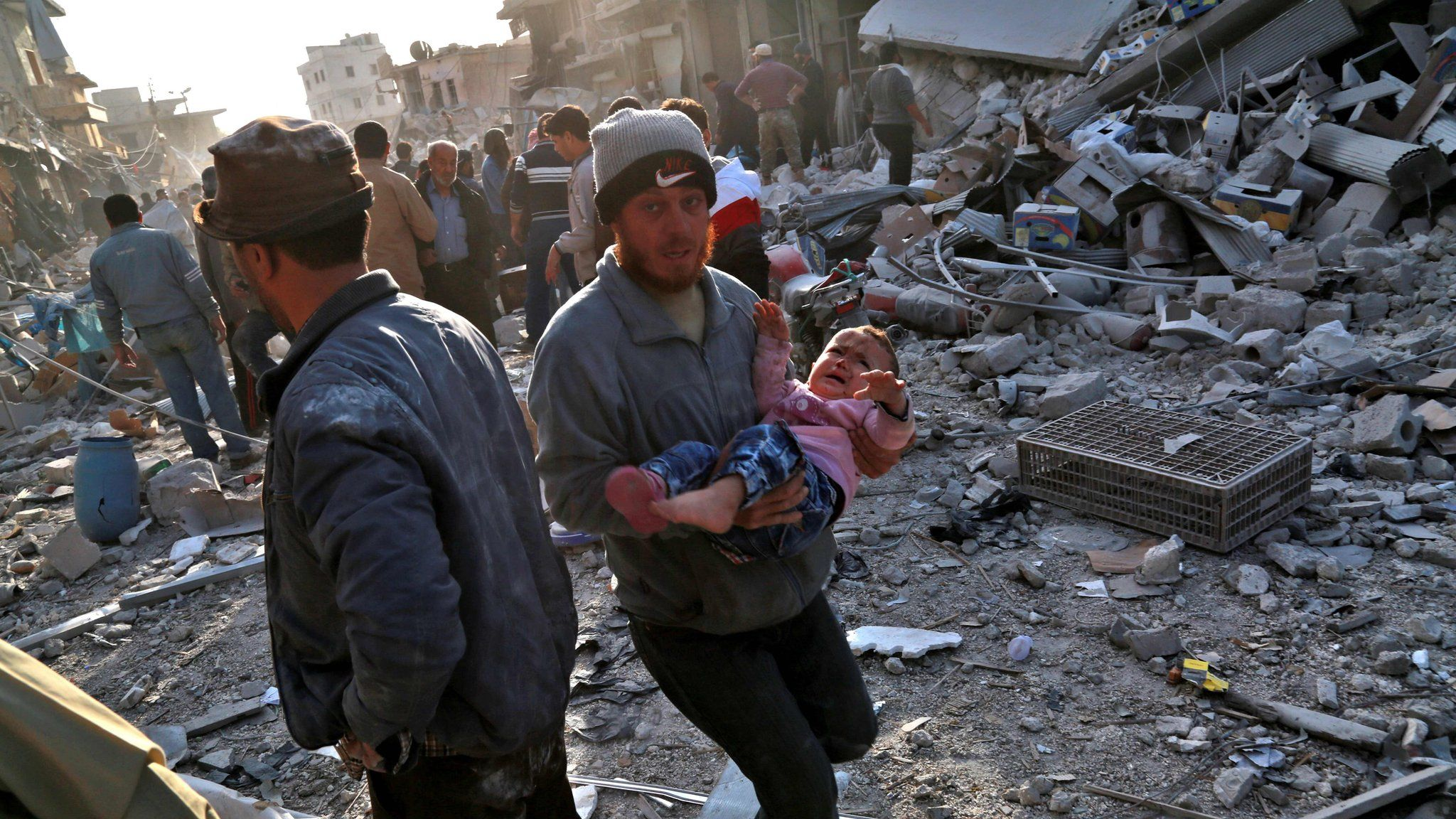 A Syrian man carries a child following a reported air strike on the rebel-held town of Atareb in northern Syria on 13 November 2017