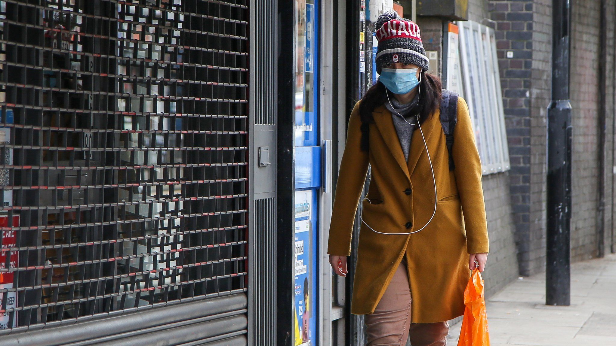 A woman wears a face covering while walking down a street in London