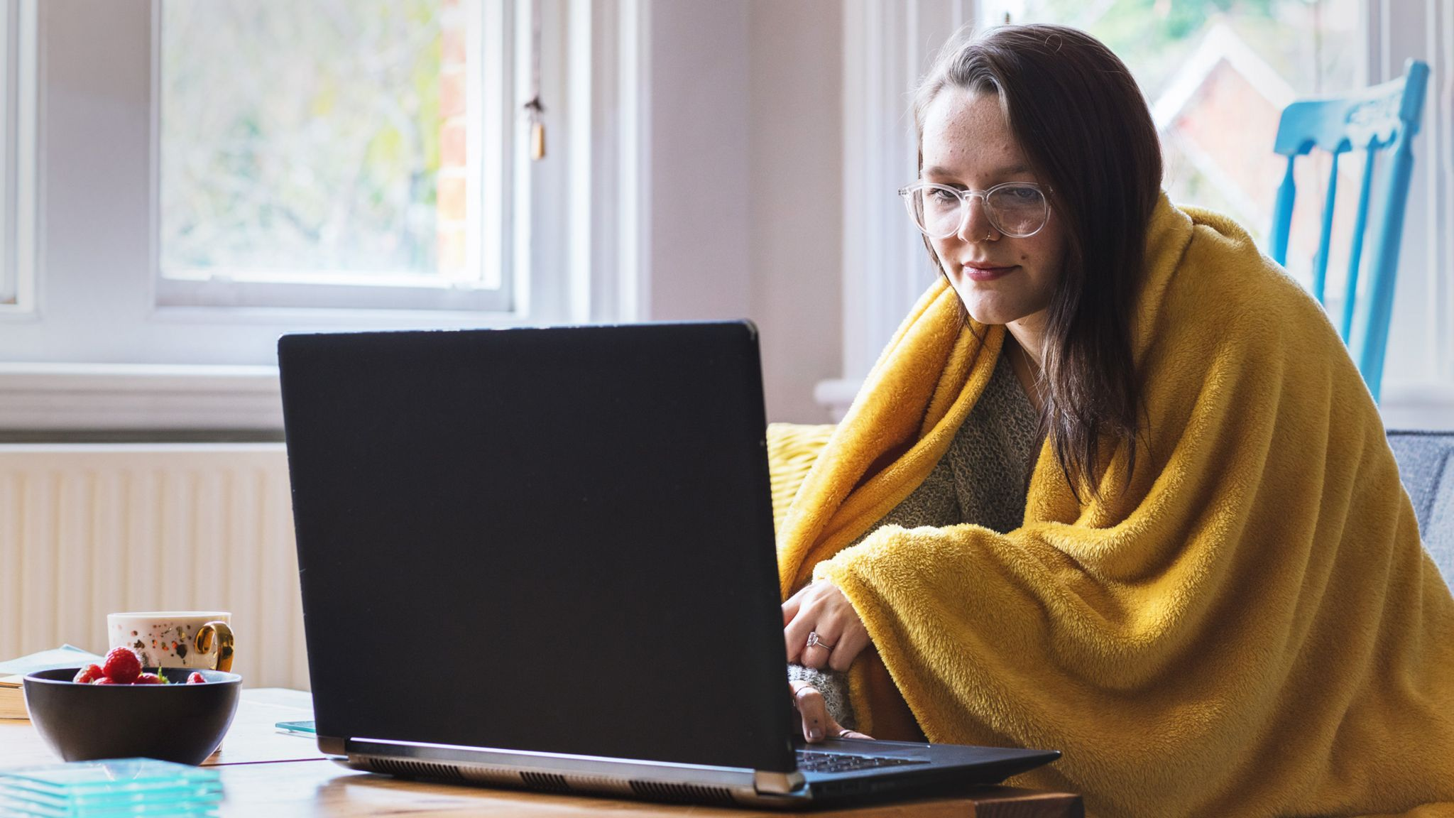 Woman home-working with a blanket over her shoulders