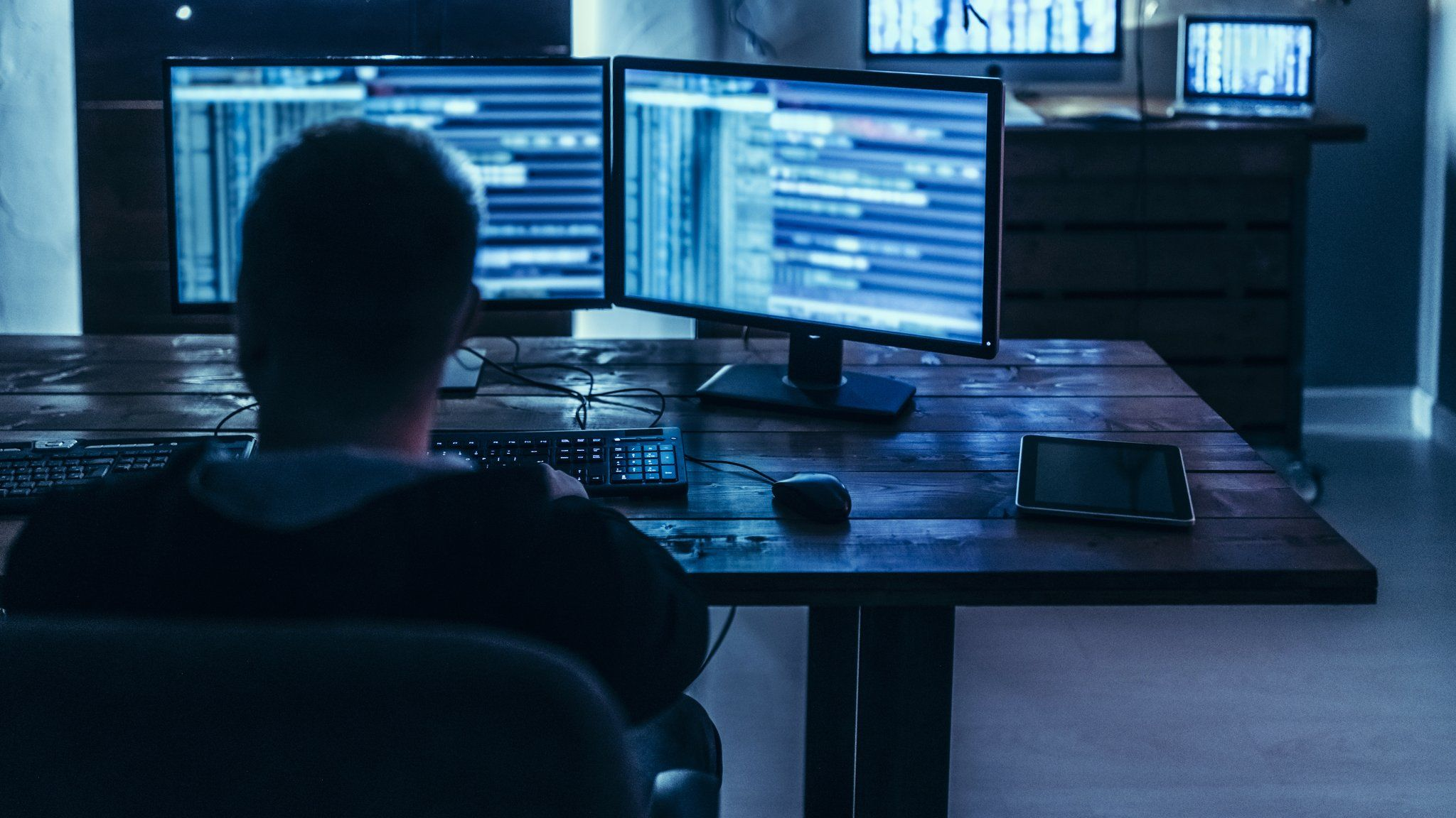 A hacker at a computer in a dark room