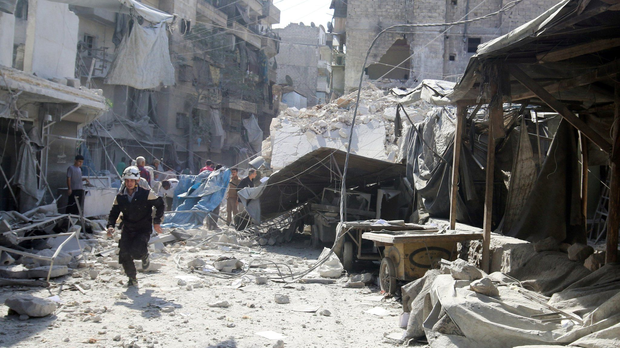 A rescue worker runs at a market hit by air strikes in Aleppo's rebel-held Fardous district, Syria (12 October 2016)