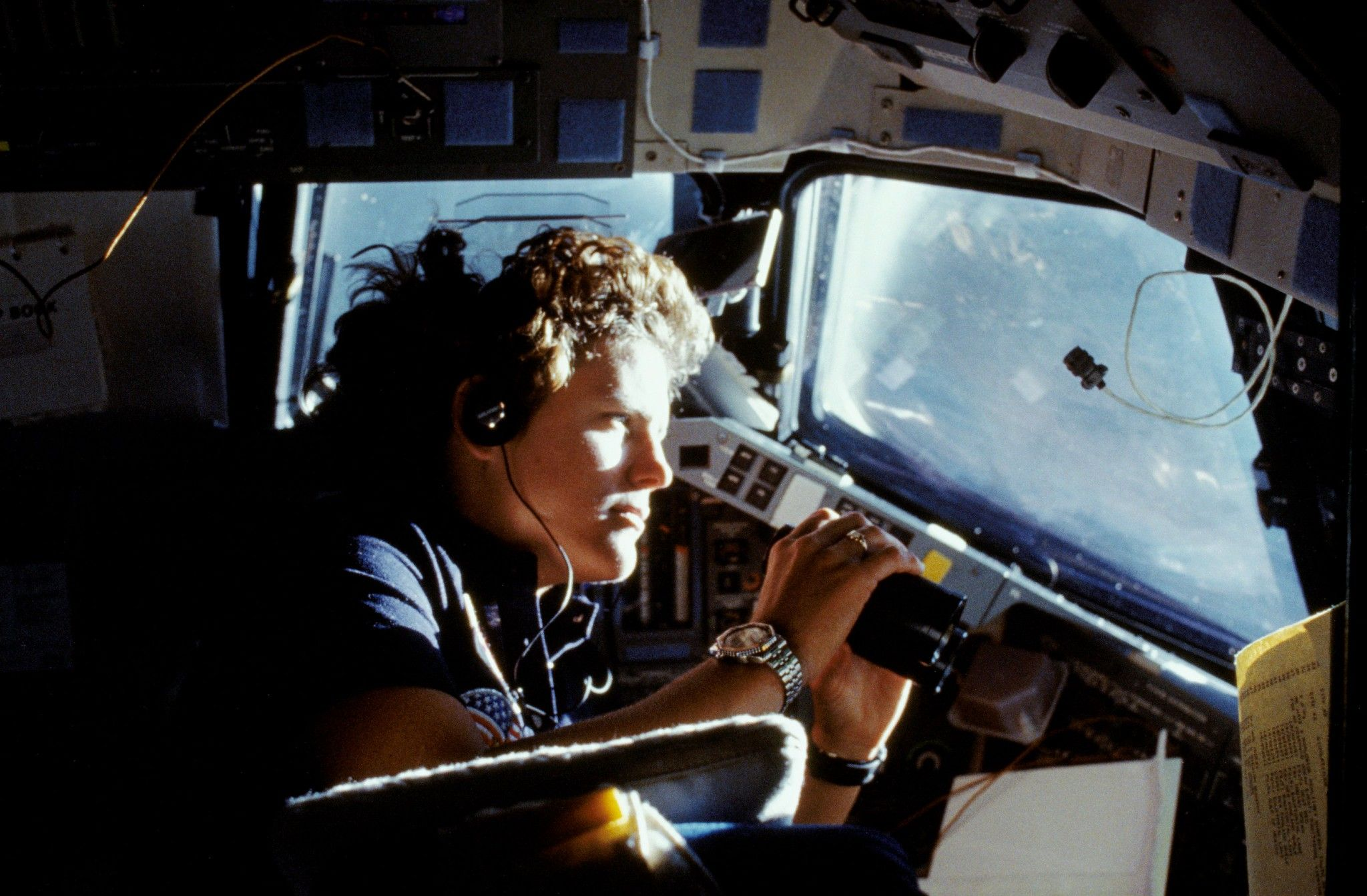 Astronaut Kathryn D. Sullivan, 41-G mission specialist, uses binoculars for a magnified viewing of earth through the forward cabin windows.