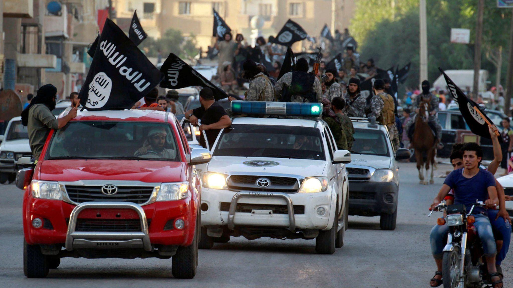 IS militant hold up black jihadist banners in Raqqa on 30 June 2014