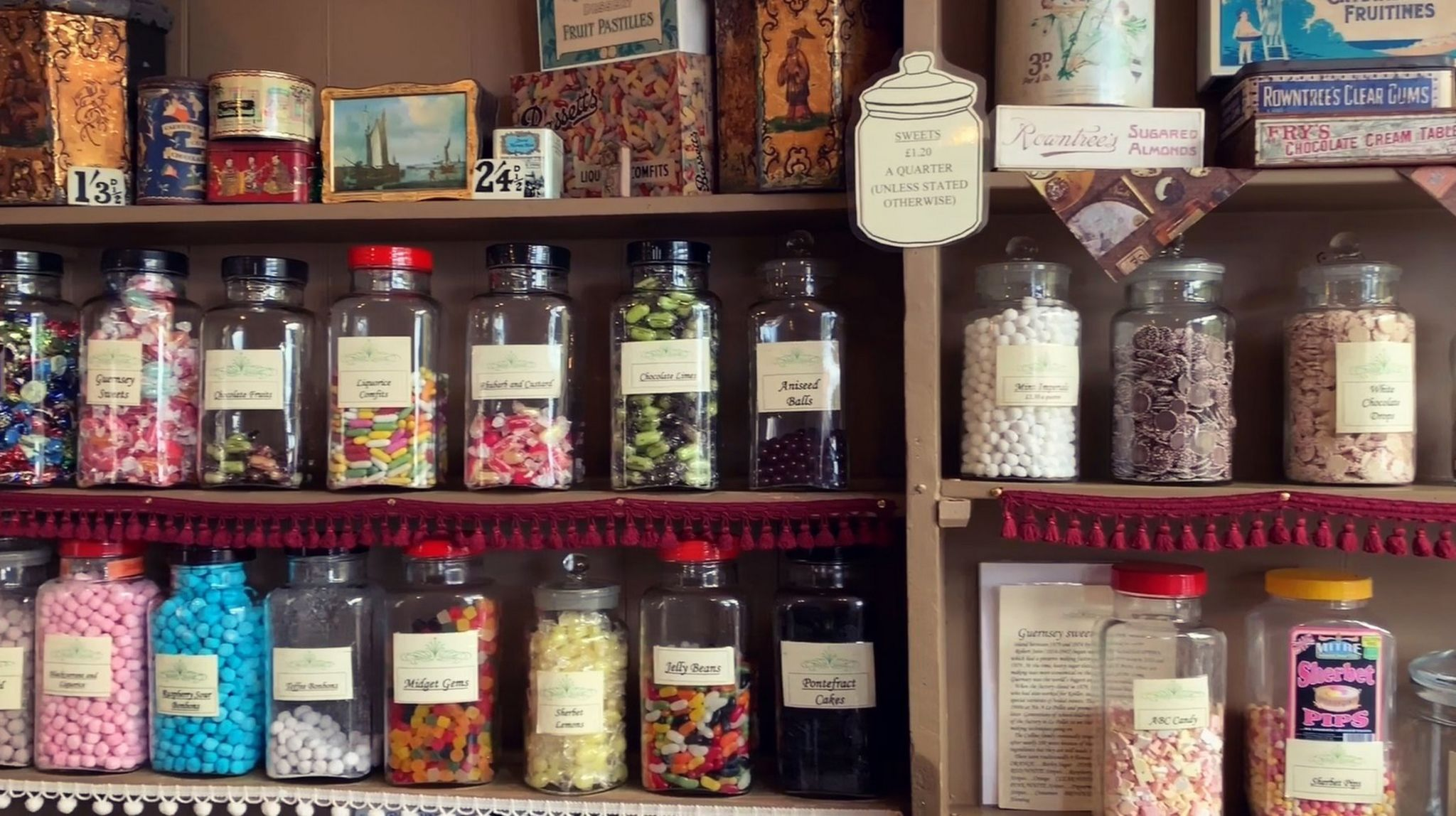Sweets in jars on shop shelves.