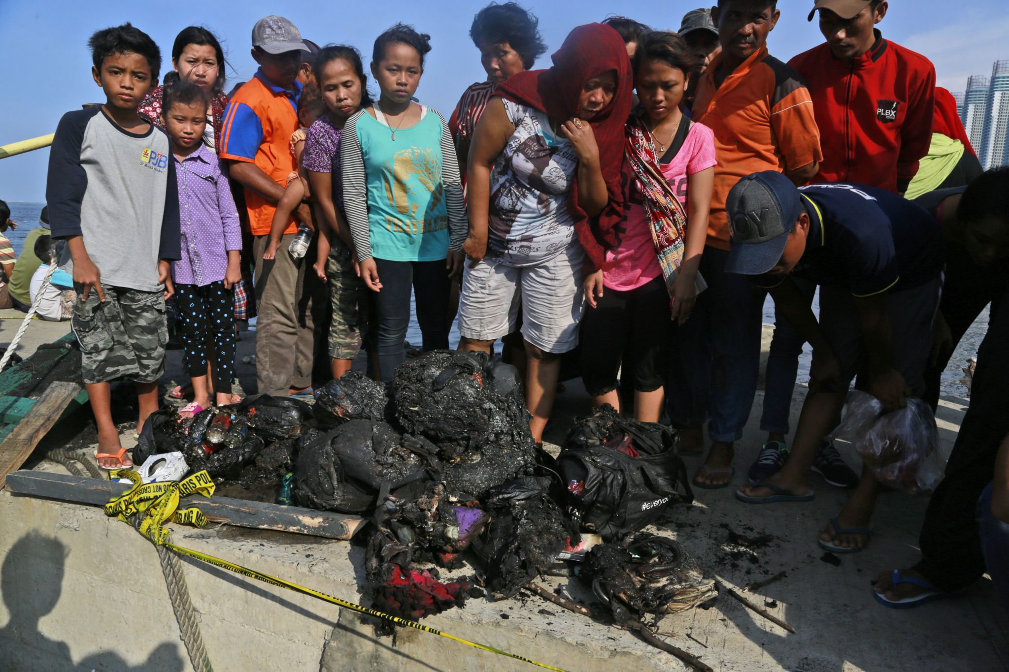 People inspect charred personal belongings of the passengers of a ferry that caught fire off the coast of Jakarta, at Muara Angke Port in Jakarta, Indonesia, Sunday, Jan. 1, 2017.