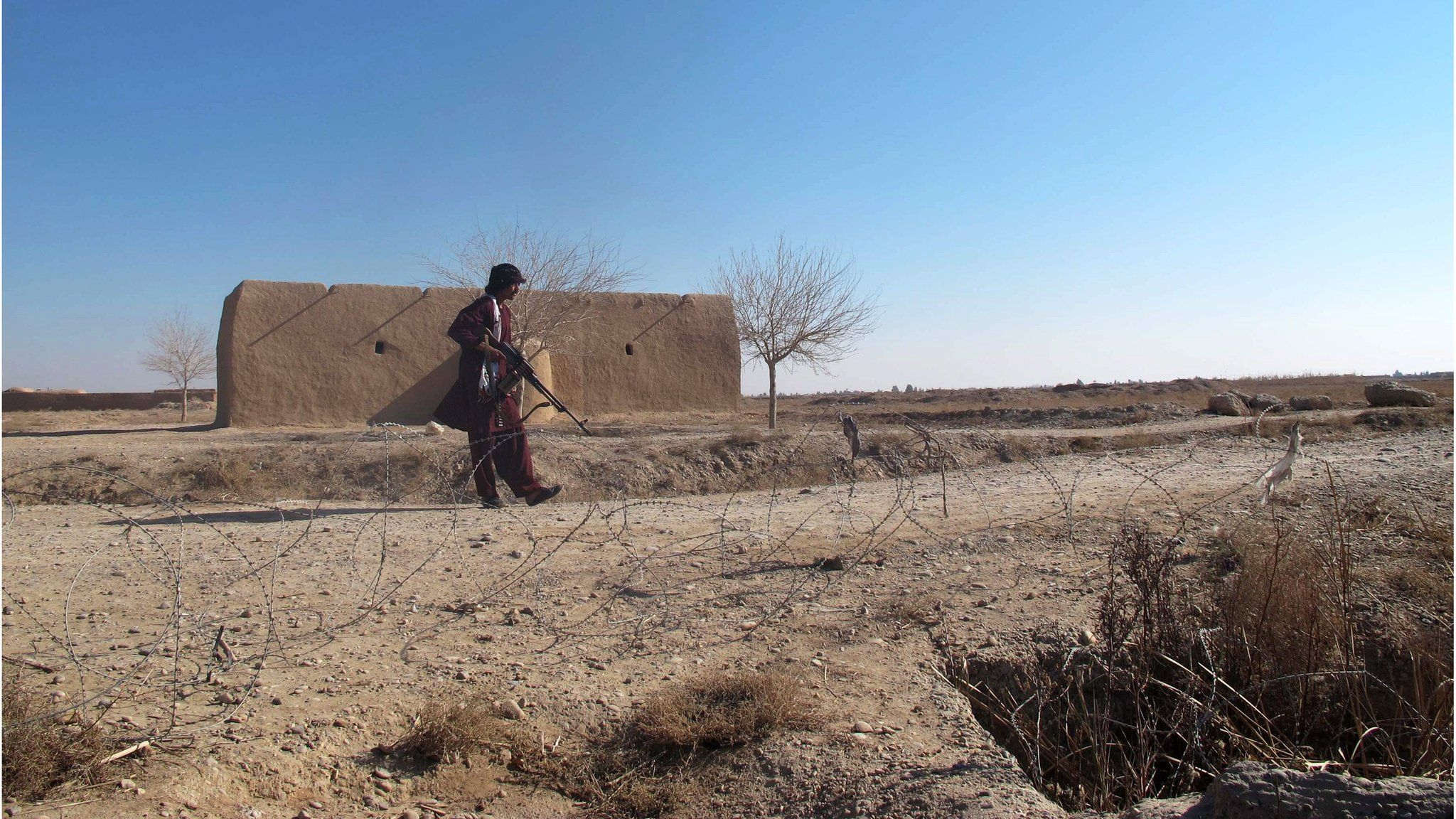 A member of the Afghan Local Police (ALP) forces stands guard on a roadside in the Nawar area of Marjah district, Helmand province, Afghanistan (23 December 2015)