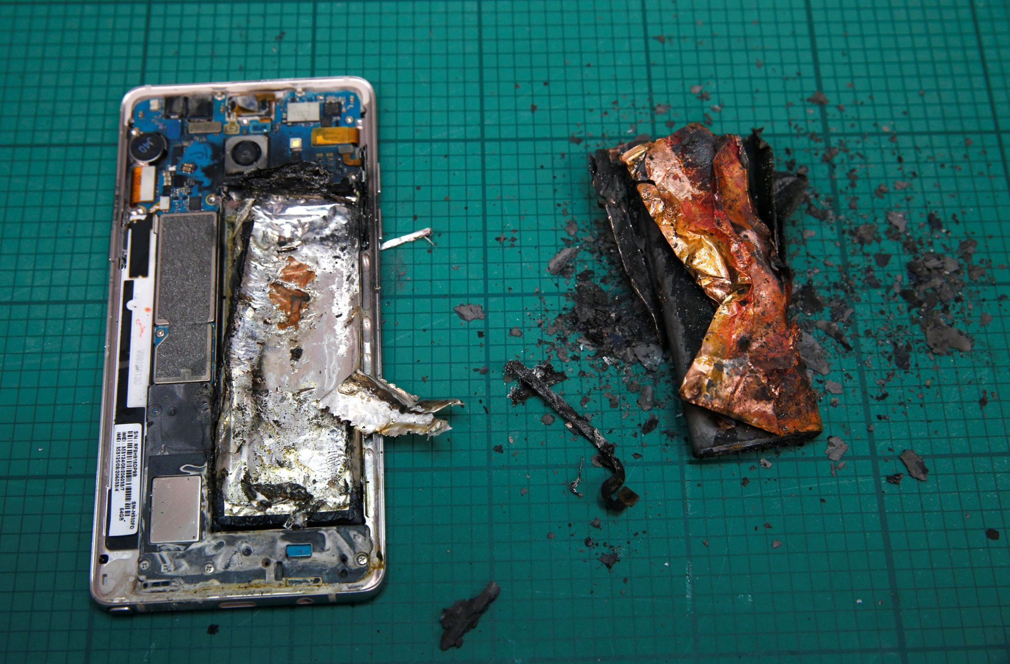 A Samsung Note 7 handset is pictured next to its charred battery after catching fire during a test at the Applied Energy Hub battery laboratory in Singapore 5 October 2016