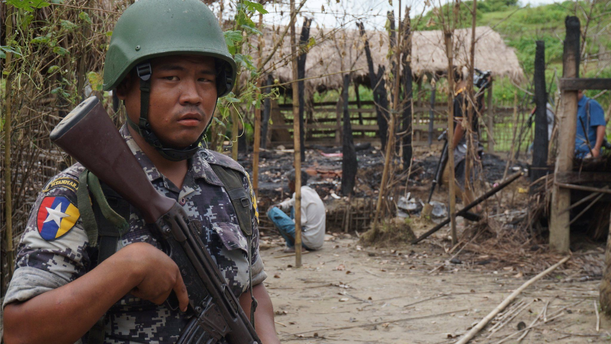 A Myanmar border guard police officer stands guard in front of the remains of a house burned down in a clash between suspected militants and security forces in Tin May village, Buthidaung township, northern Rakhine state, Myanmar 14 July 2017