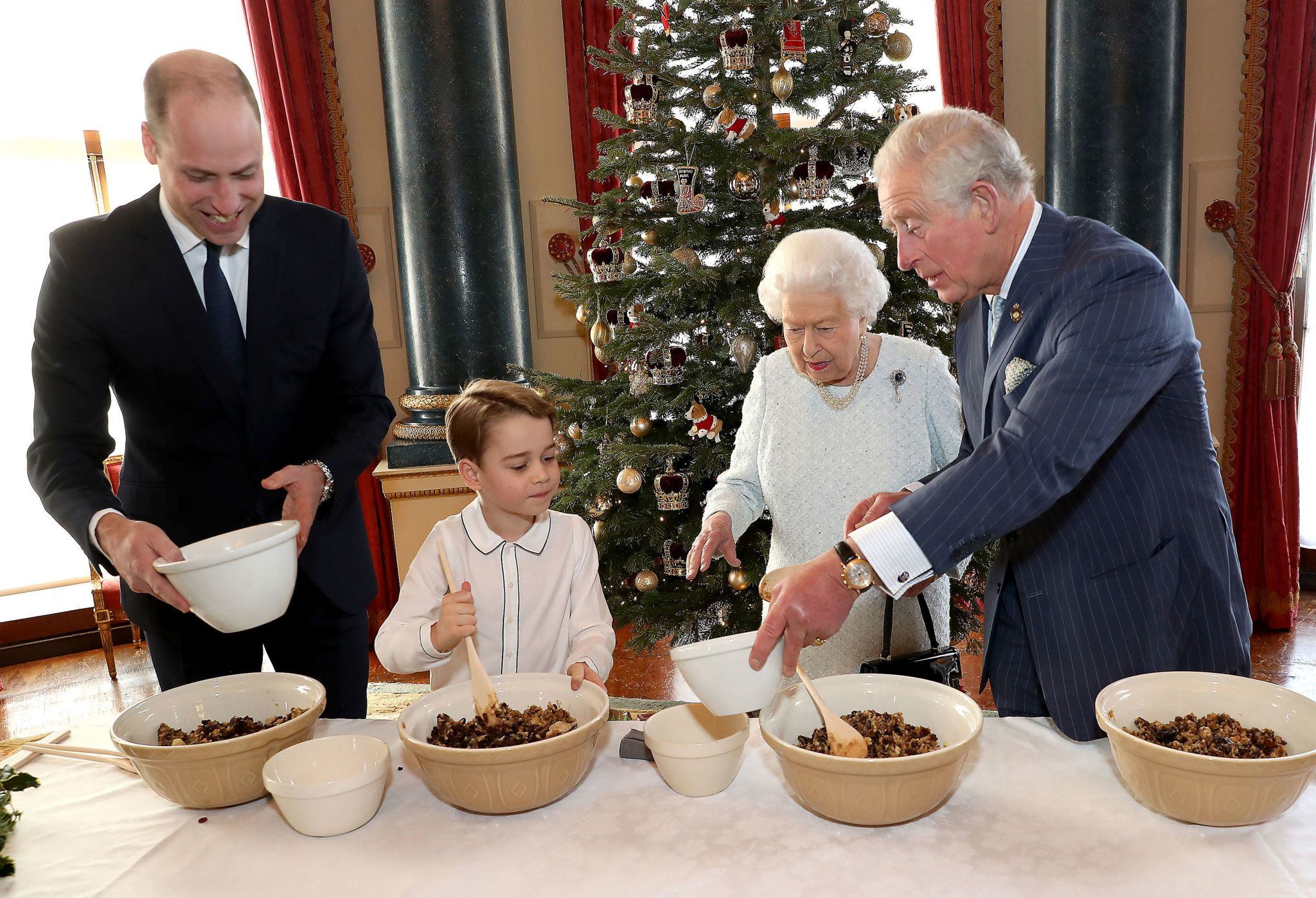 "Queen Elizabeth II, the Prince of Wales, the Duke of Cambridge and Prince George preparing special Christmas puddings in the Music Room at Buckingham Palace, London, as part of the launch of The Royal British Legion""s Together at Christmas initiative"