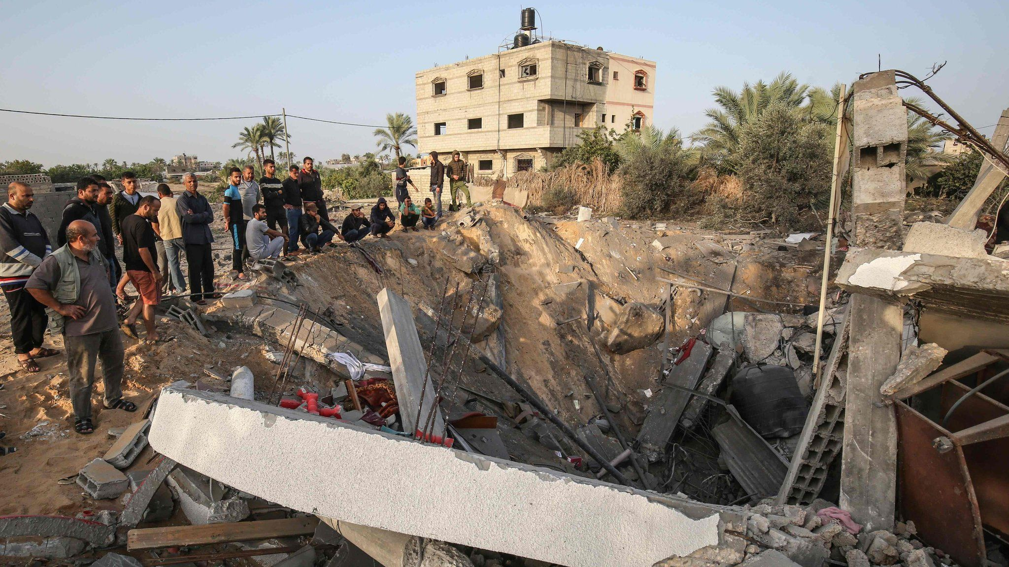Palestinians gather around the remains of a building destroyed in an Israeli air strike in the southern Gaza Strip (13 November 2019)