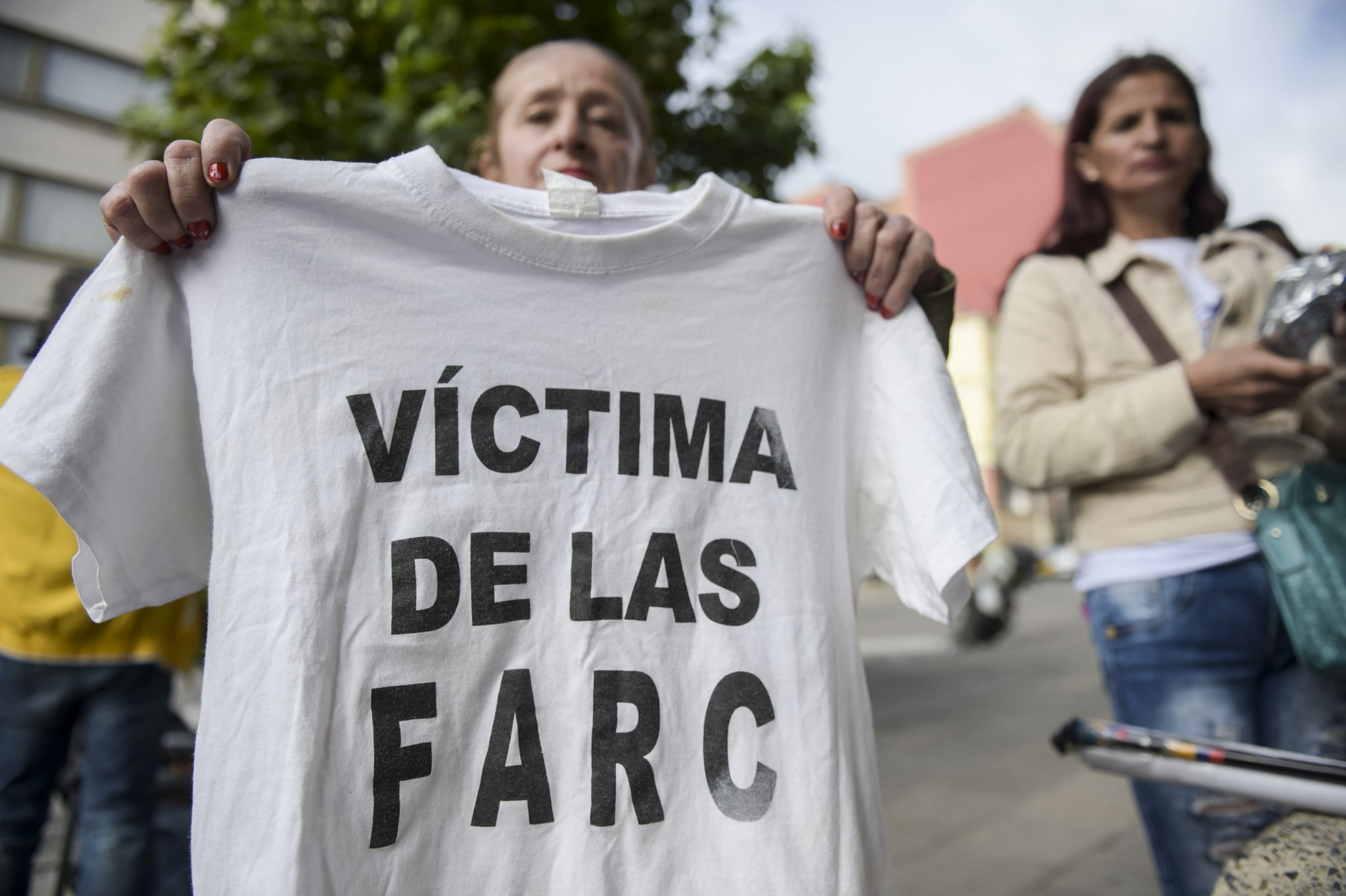 """A woman holds up a T-shirt reading """"Victim of the Farc"""" outsider the JEP in Bogota"""