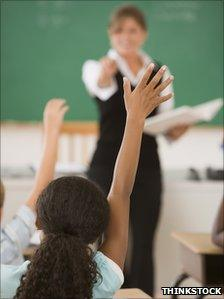 Students in a classroom raise their hands to answer the teacher's question