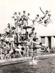 A black and white photo of boys jumping off the diving board