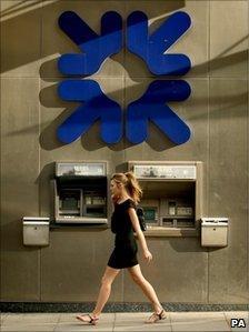 Woman walks past an RBS branch