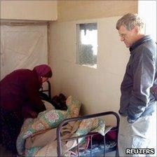 Tom Little watches as an unidentified doctor examine a patient in an Afghan clinic
