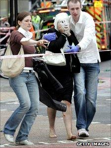 Davinia, her face covered in with a gauze mask, is helped by Paul Dadge and another volunteer who carries Davinia's shoes and jacket