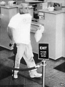 Brian Wells, holding the walking stick gun, caught on CCTV