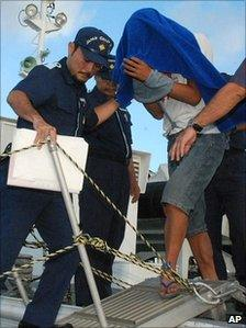 Chinese boat captain Zhan Qixiong, right, is led by Japanese coast guard officials
