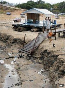 People walk on the dry river bed in Marina do David, on the outskirts of Manaus