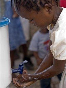 A young girl is properly washing her hands at health clinic in Gaston Margron.