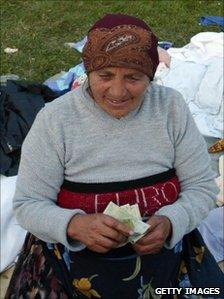 Romanian lady counts her lei