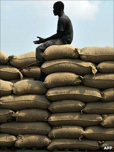 A man stands next on cocoa bags in front of a warehouse at the Abidjan port on December 9, 2010