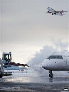 An aircraft takes off as another is de-iced at Copenhagen's Kastrup International Airport, 21 December 2010
