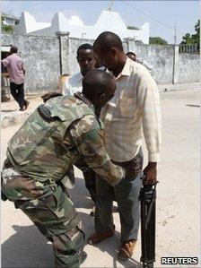 Ugandan peacekeeper searches a journalist in Mogadishu, Somalia, on 30 December 2010